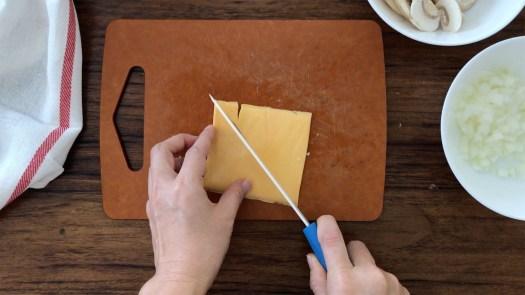 Cutting a slice of Cheddar cheese diagonally