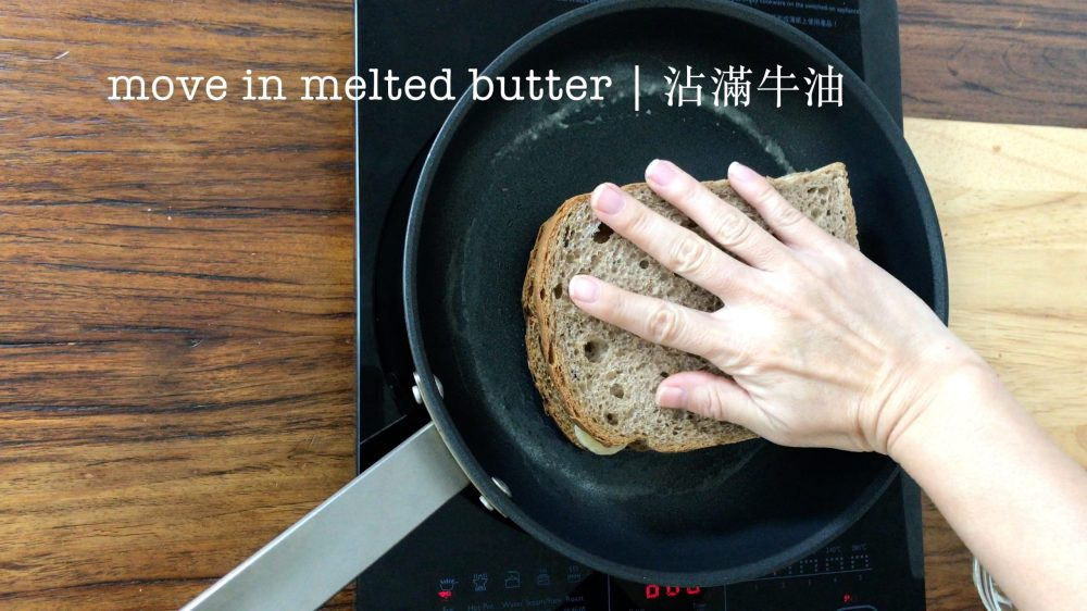 moving the sandwich around to absorb all the melted butter in the pan