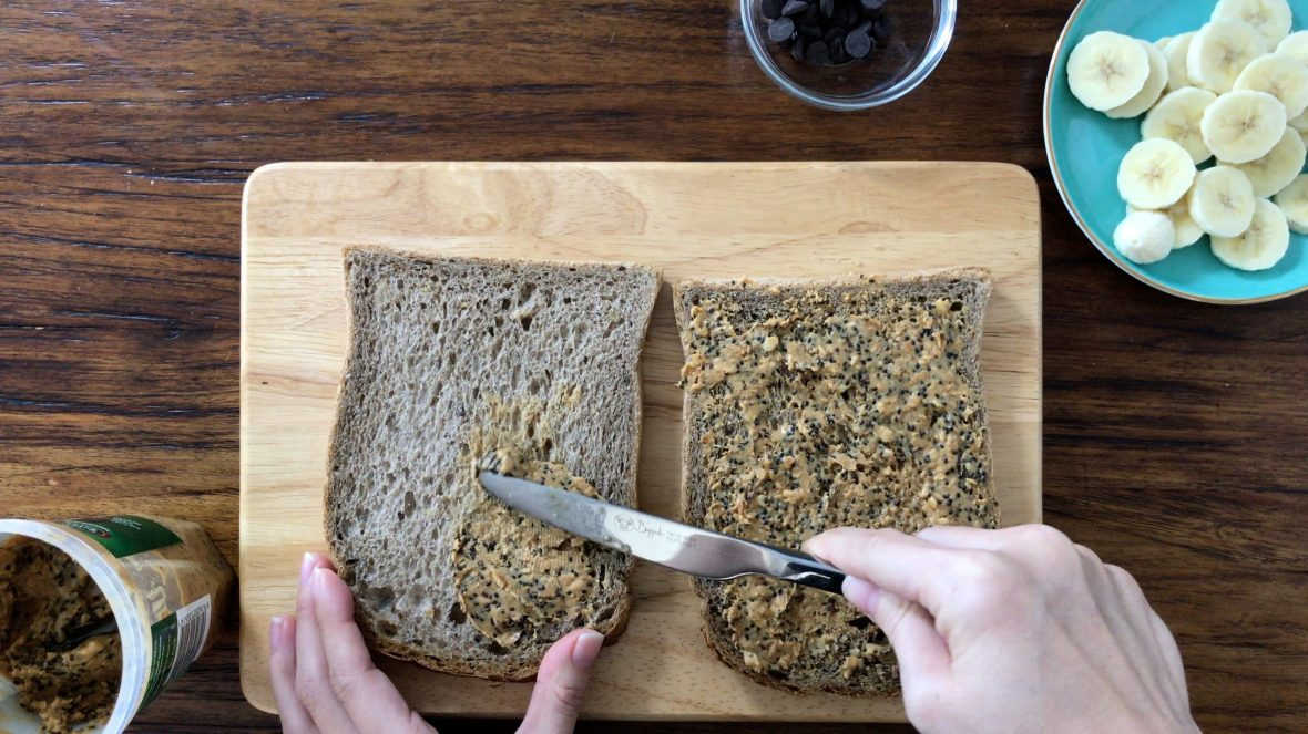 Spreading peanut butter on the brown bread