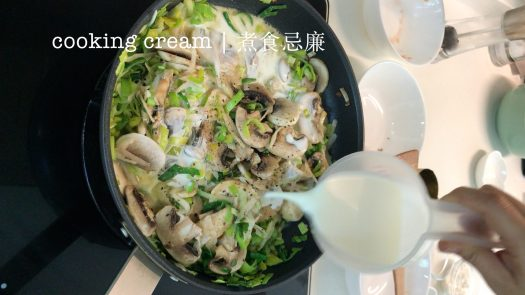 Pouring some cooking cream into a pan with sliced mushrooms, grated potato and chopped leek