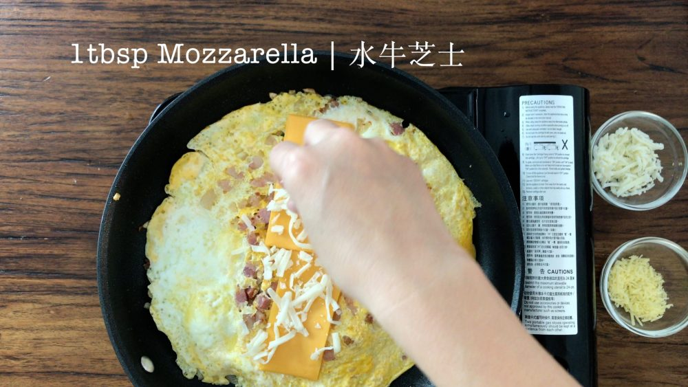 Place grated Mozzarella cheese on top of the tortilla with egg mixture