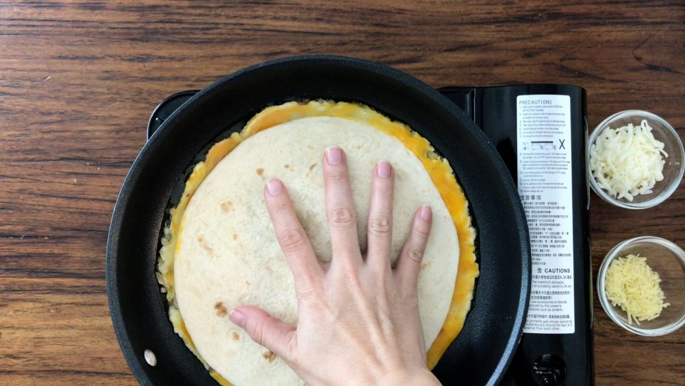 Cover the egg mixture in the pan with a tortilla and press with a hand