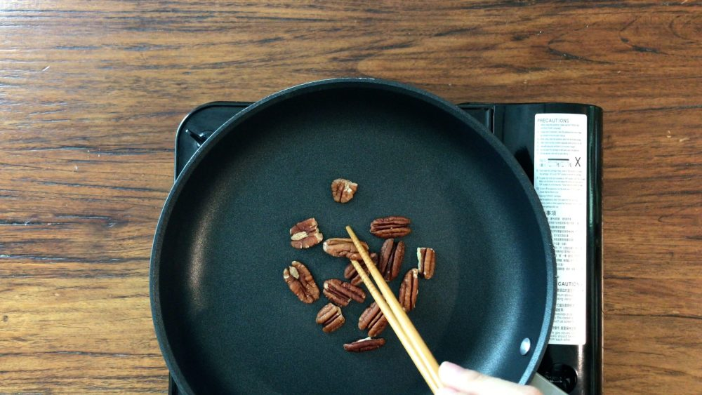 Brown the pecans in a dry pan