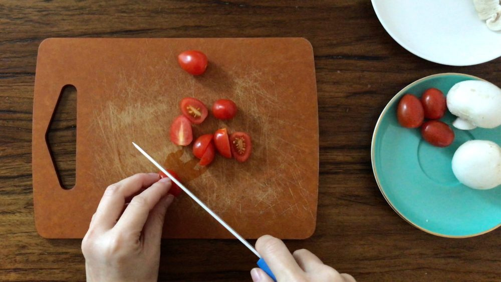 halve a few cherry tomatoes on a chopping board