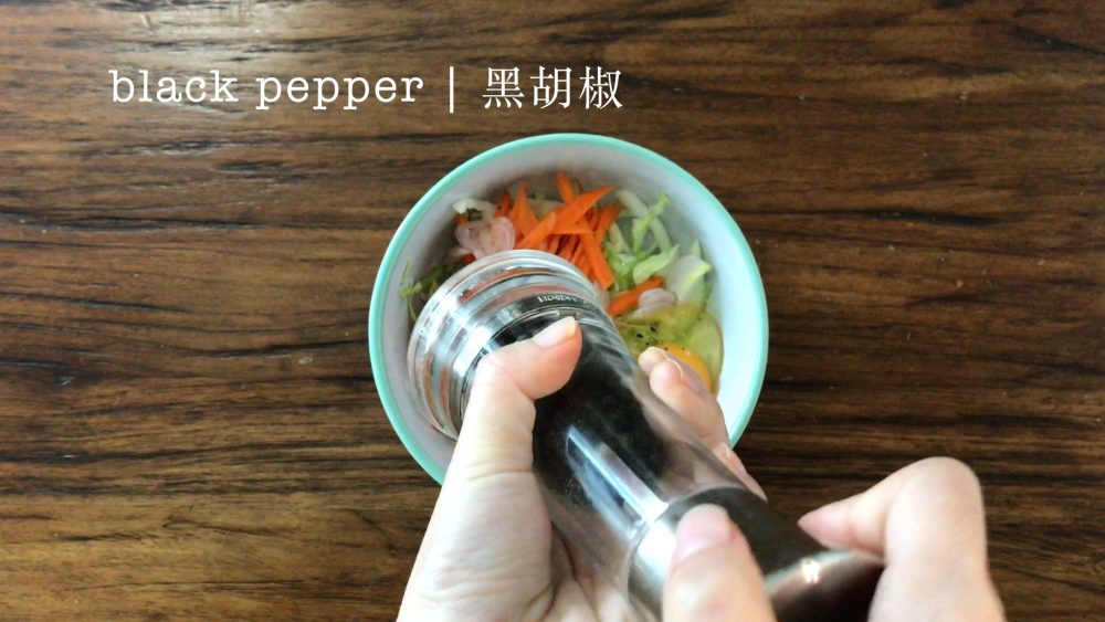 Adding some black pepper into a bowl with mixed vegetables and egg