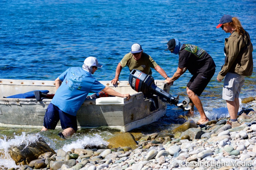 Kenny, Alec and Ryan steady the skiff as Kim Hull boards