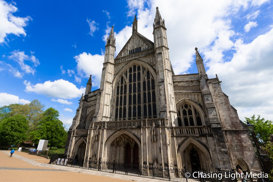 Winchester Cathedral against a blue sky with scattered clouds