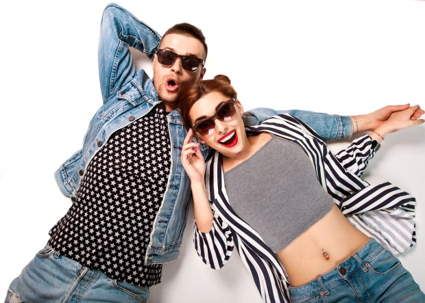 fashion couple in sunglasses lies on a white background, smiling happily and surprised
