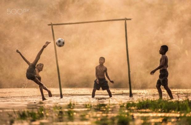 Asia Boy kicking a soccer ball