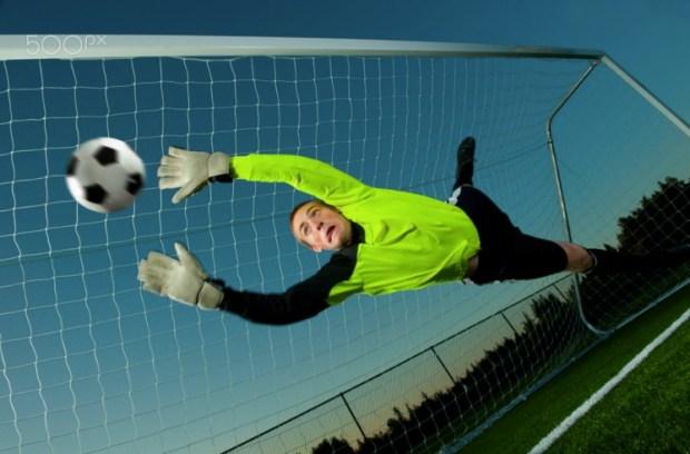 Caucasian soccer goalie jumping
