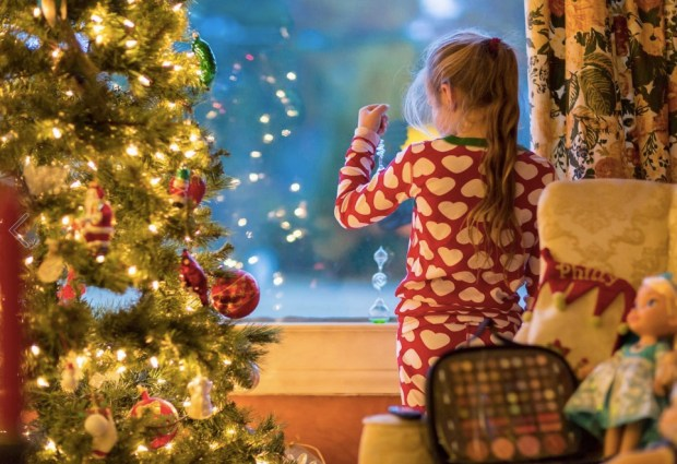 Caucasian girl looking out window near Christmas tree
