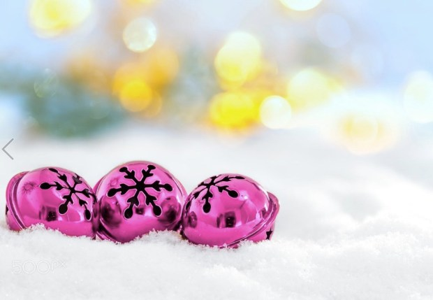 Christmas jingle bells on snowy background and defocused lights
