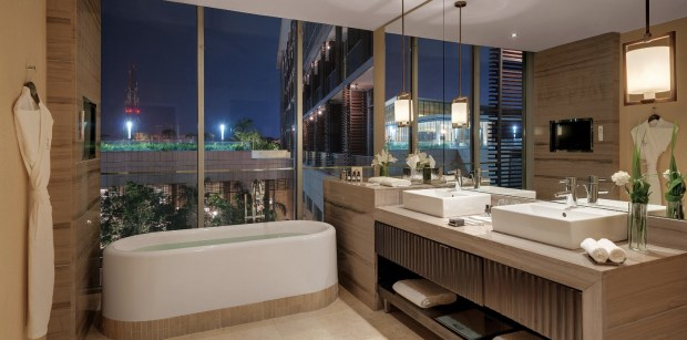a-bathroom-with-large-mirrors-and-windows-overlooking-the-courtyard-of-the-kempinski-hotel-in-accra-ghana