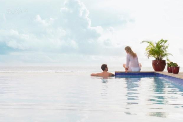Caucasian couple relaxing at pool