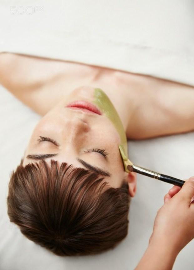 Woman having facial mask in spa