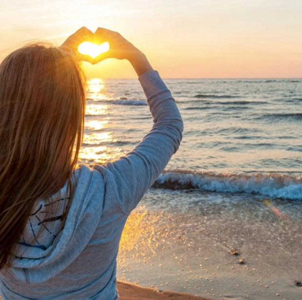 girl-holding-hands-in-heart-shape-at-beach