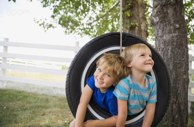 Playful boys on a tire swing