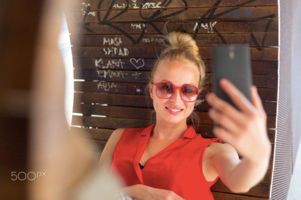 Young cheerful lady taking selfie