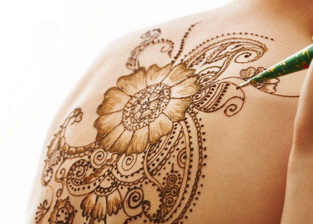 Model's back with beautiful pattern of henna