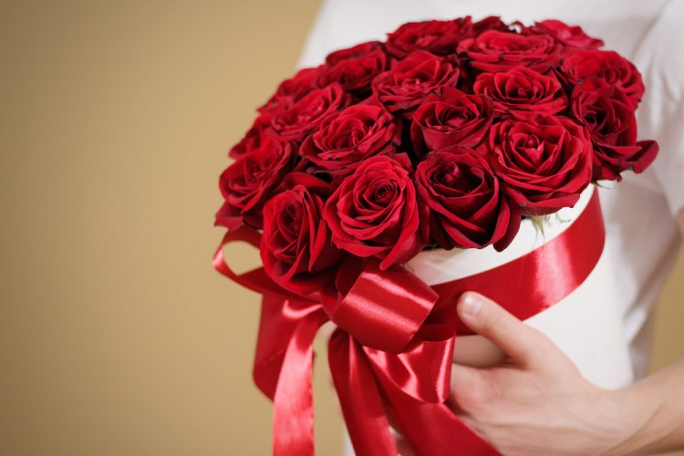 Man in white t shirt holding in hand rich gift bouquet of 21 red roses