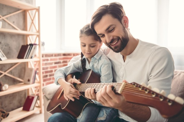 Cute little girl and her handsome father are playing guitar