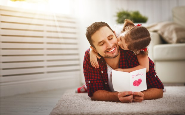 Happy family daughter kiss dad and giving greeting card
