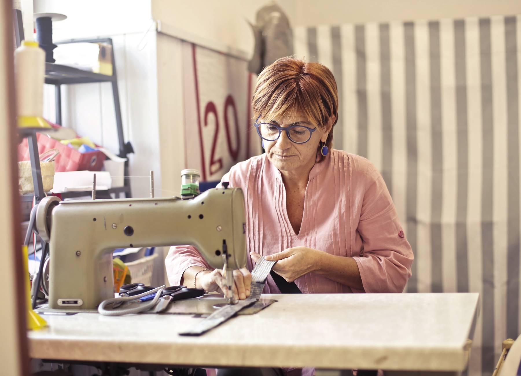 photo of woman using sewing machine