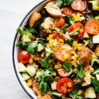 Tomato panzanella with corn, cucumbers, and herb salad