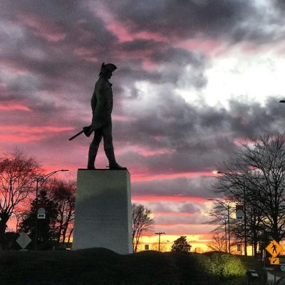 a view of nathaniel greene statue with the setting sun