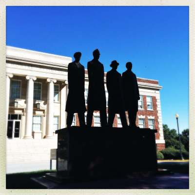 a photo of a statue of the a&t four from the greensboro sit-ins on the campus of a&t university the statue is in shadow with the dudley memorial building lit up behind it by the sunshine