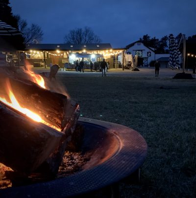 a photo at dusk with a fire pit in the foreground and a food and drink truck in the background at summerfield farms in greensboro nc