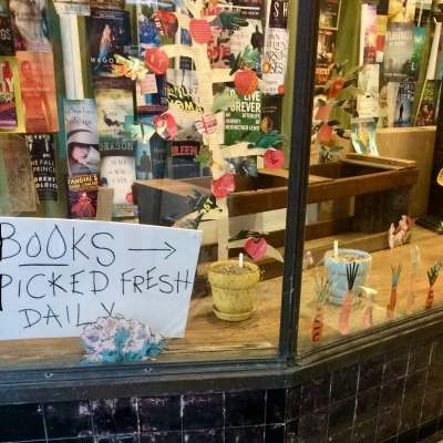 """a photo of the outside window of scuppernong books in greensboro nc with a sign in the window that says """"books picked fresh daily"""""""