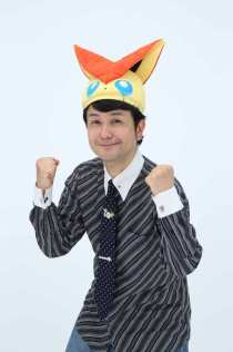 Hidenori Kusaka, posando divertido con una corbata sobre Pokémon, y un gorro de Victini