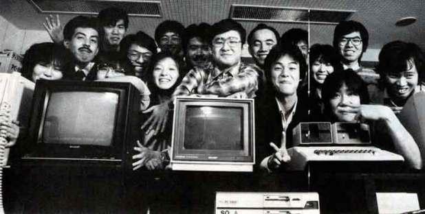 Masafumi Miyamoto (centro, con gafas), junto a Hironobu Sakaguchi (justo a la derecha de Miyamoto) y Hiromichi Tanaka (ambos realizando el gesto de la victoria, si bien Tanaka tapa parcialmente su rostro con su mano izquierda), con el resto del equipo de lo que posteriormente sería Square Co. Ltd.