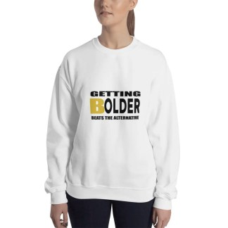 Woman with shoulder length dark brown hair & dark jeans wearing a white sweatshirt with a slogan which says getting bolder beats the alternative.