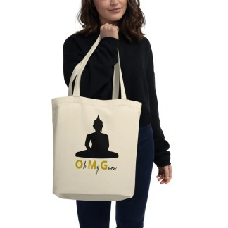 Woman in black holding a natural coloured cotton tote bag with silhouette of Tibetan Buddha with the phrase oh my guru underneath