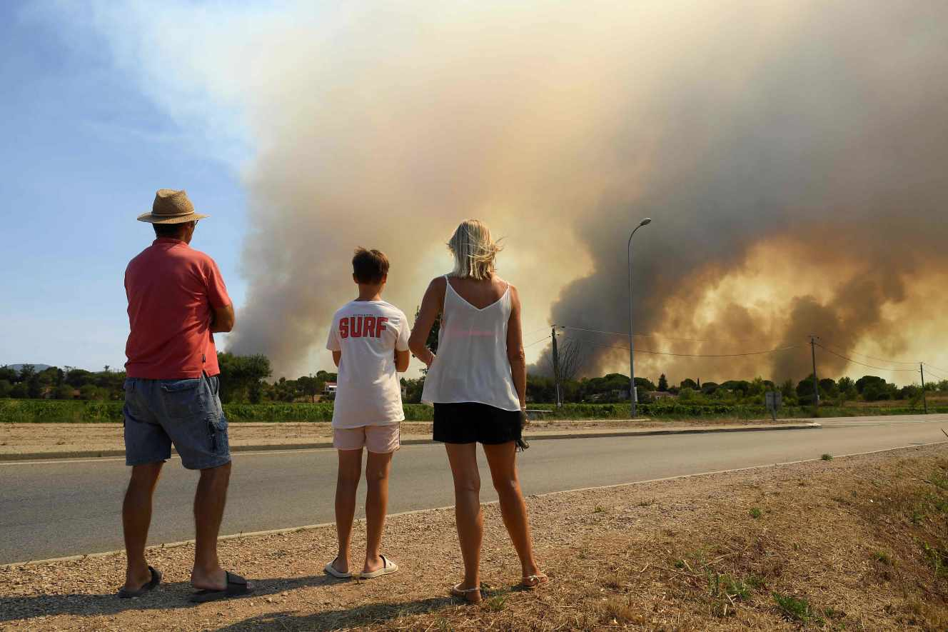 TOPSHOT - Tourists watch from the roadside as dense smoke darkens the sky from reignited forest fires north of Grimaud, in the department of Var, southern France on August 18, 2021. Hundreds of firefighters struggled for a third day on August 18 to contain France's worst wildfire of the summer near the glitzy Riviera resort of Saint-Tropez which has left one person dead and forced thousands of residents and tourists to flee. Around 750 firefighters and water-dropping aircraft were battling the blaze in difficult conditions, with high temperatures and strong winds. (Photo by NICOLAS TUCAT / AFP)