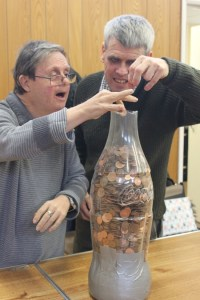 two men putting pennies in a bottle