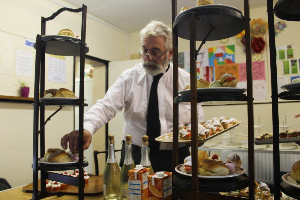 a man arranging cakes in kitchen