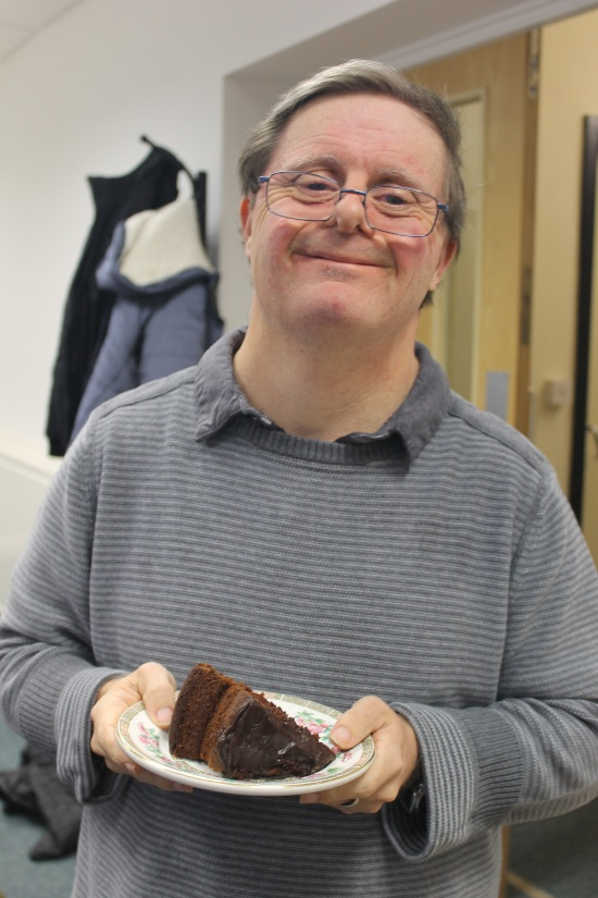 a man holding some chocolate cake