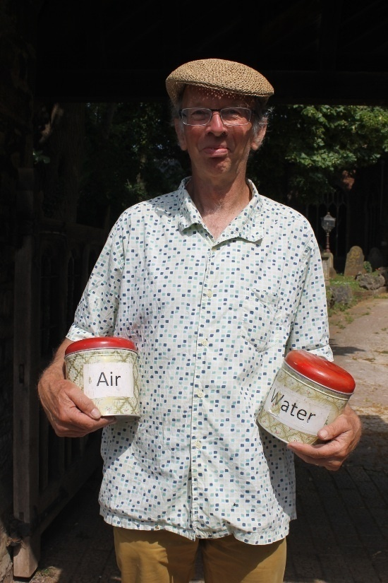 a man holding two jars one labelled air the other labelled water