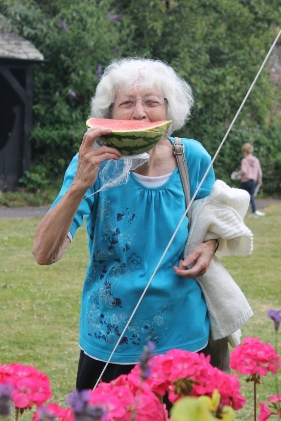 a woman in a blue top holds a piece of melon up to her face like a smile