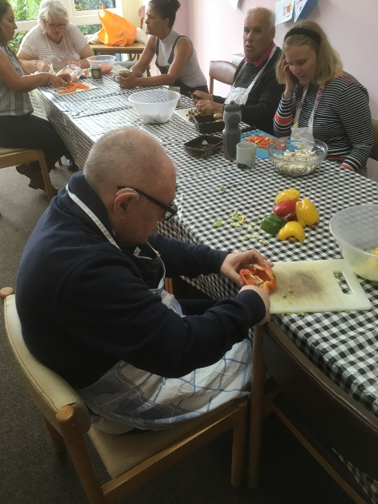 people are sitting around a table with a black and white check table cloth, chopping and preparing food