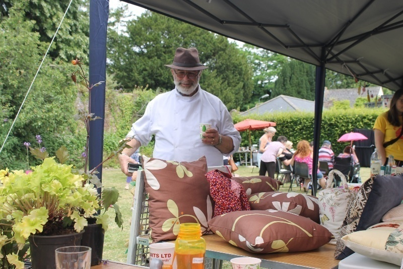 a man in chefs clothes and a brown hat has a cup of tea while looking at some craft furnishings on the Phoenix stall