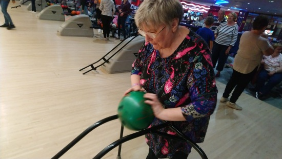 a woman is picking up her green bowling bowl ready for some ten pin bowling