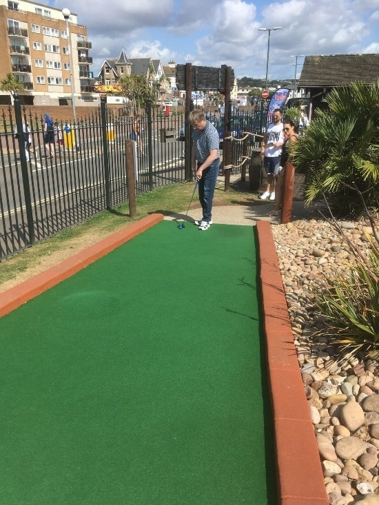 a man in a stripy top is putting on a crazy golf course