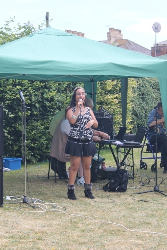 a woman in a black and white top and black skirt is singing under a green gazebo