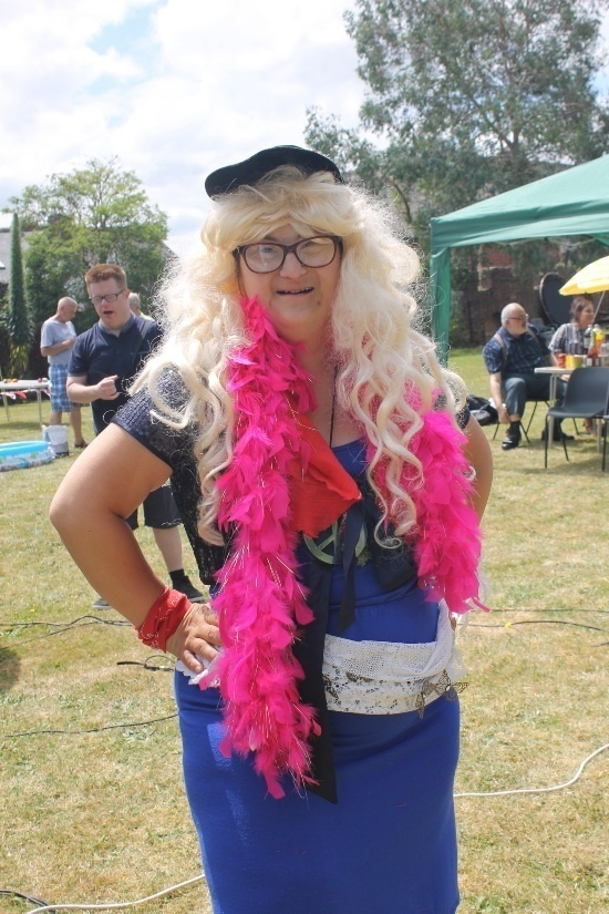 A women in a fancy blue dress wearing a blonde wig and a pink feather boa