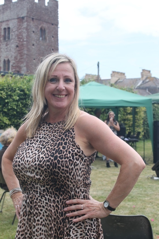 a woman with blond hair and a tiger print top has her hands on her hips looking at the camera