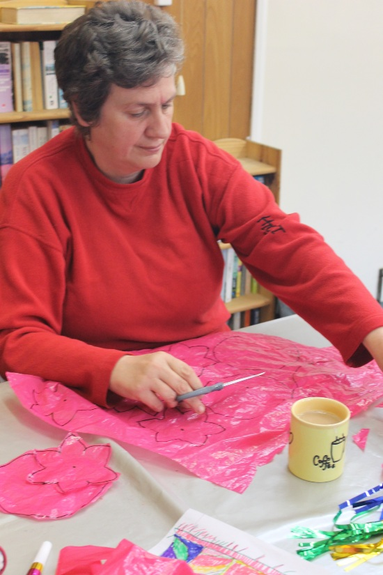 a woman is cutting out 'petals' from a pink plastic bag